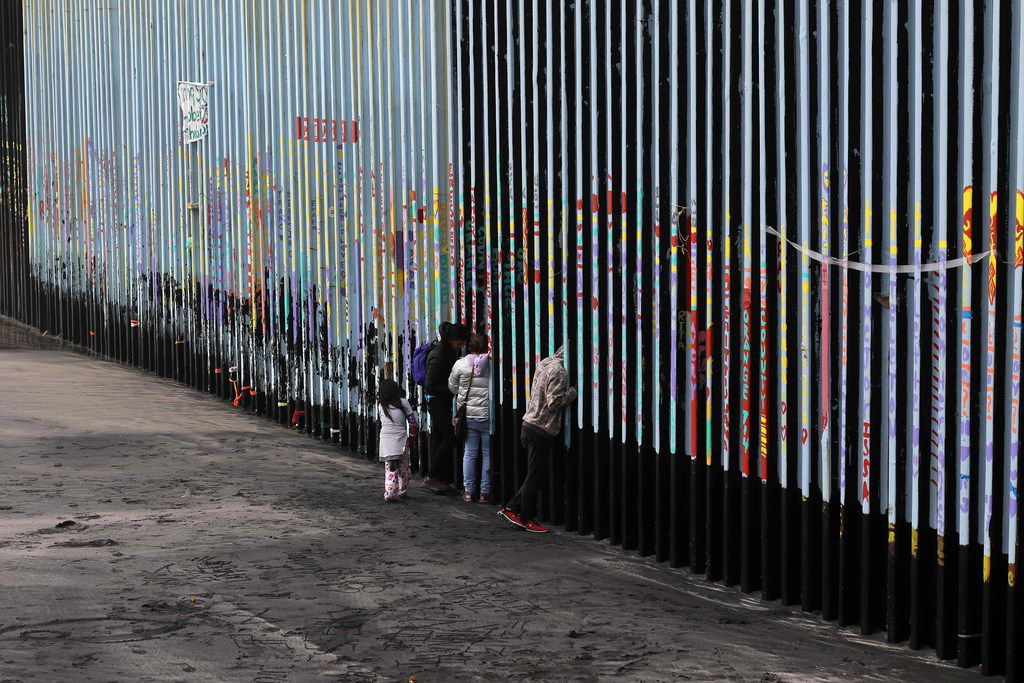 A family of Central American migrants look through the US-Mexico border fence, as seen from Playas de Tijuana, in Baja California state, Mexico, on Jan. 16, 2019