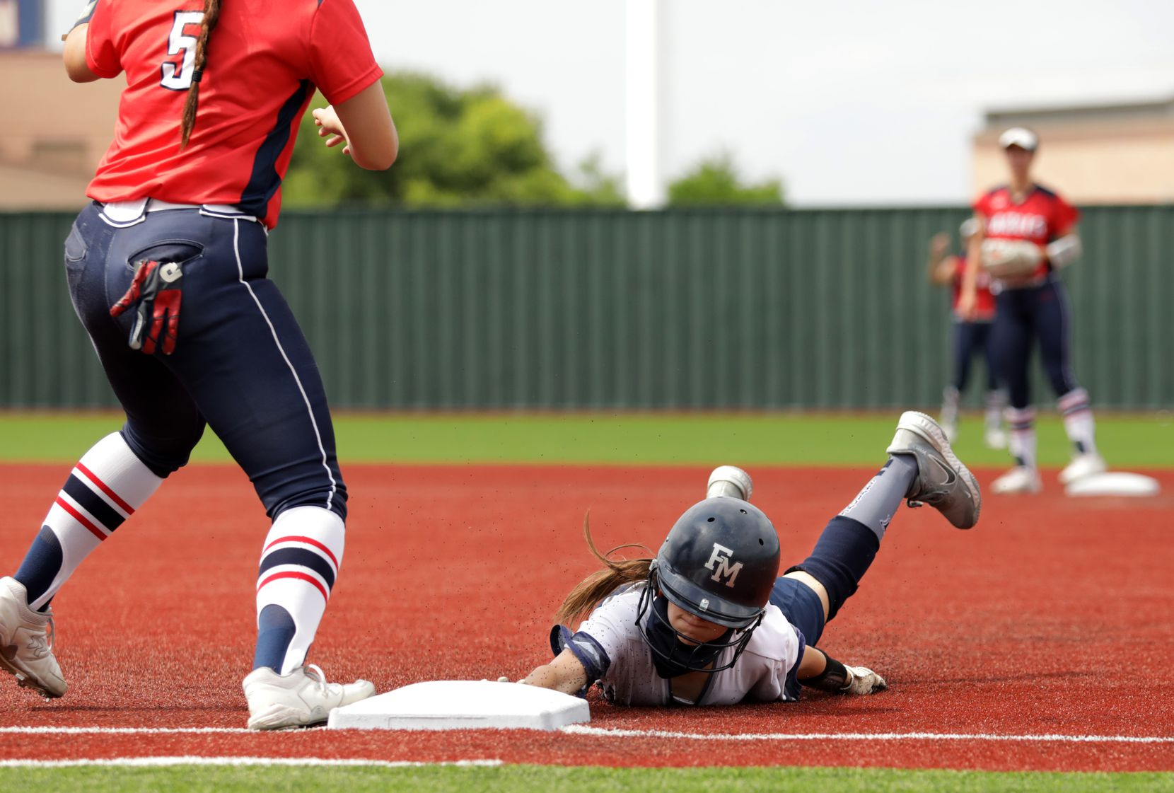 Flower Mound High School player #7, Logan Halleman, slides back into first base as Allen High School player #5, Brooklyn Purtell, attempts to get stop her during a softball playoff game at Allen High School in Allen, TX, on May 15, 2021. (Jason Janik/Special Contributor)