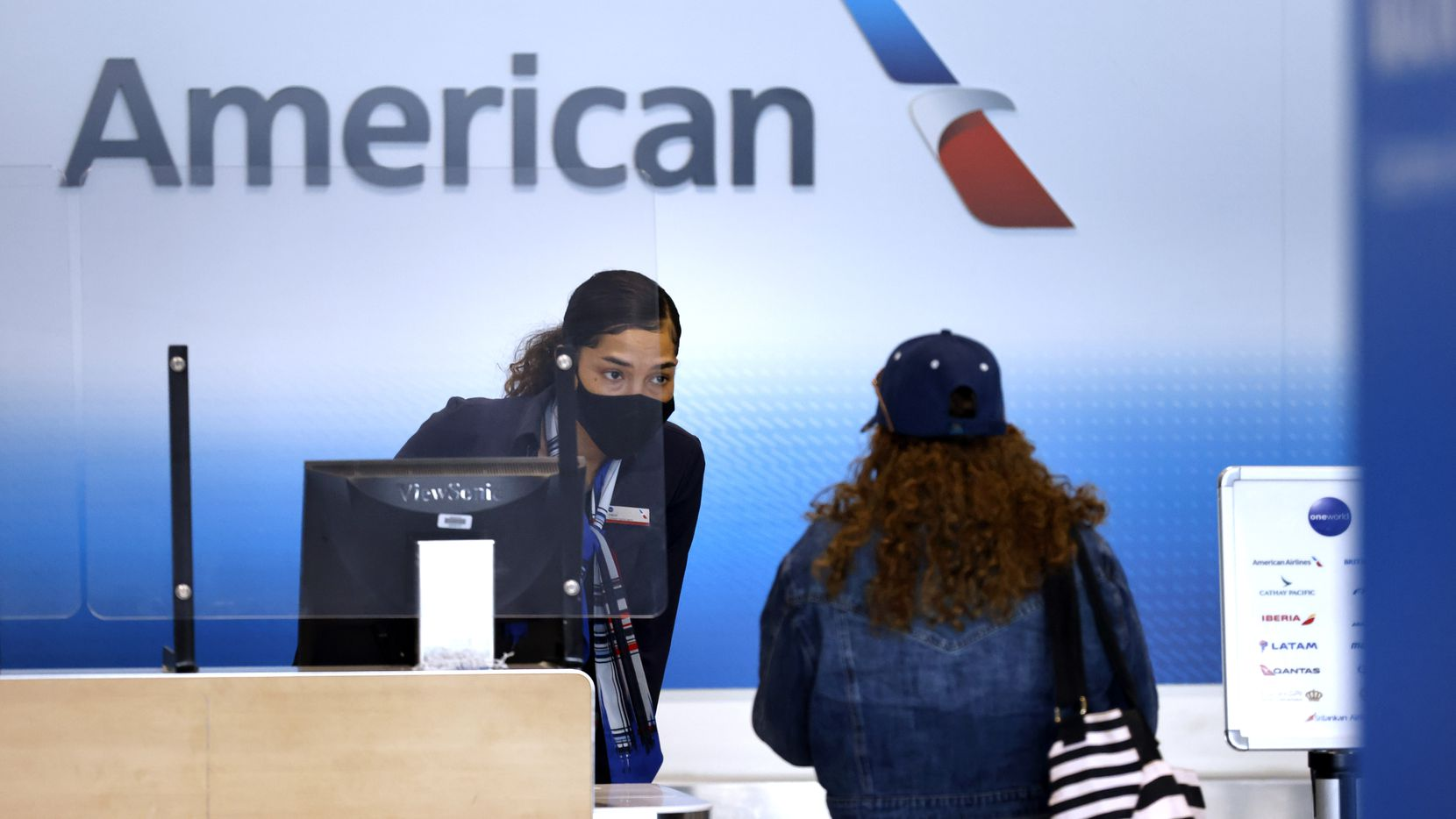 An American Airlines customer assistance representative checks-in a passenger in Terminal A at Dallas-Fort Worth International Airport, Wednesday, March 24, 2021. (Tom Fox/The Dallas Morning News)