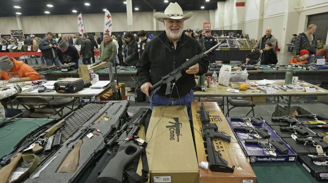 """FILE - In this Jan. 6, 2013 file photo, Ken Haiterman, of Pioneer Market, holds a CMMG 5.56mm AR 15 during the 2013 Rocky Mountain Gun Show in Sandy, Utah. A bipartisan quartet of senators, including two National Rifle Association members and two with """"F"""" ratings from the potent firearms lobby, are quietly trying to reach compromise on expanding the requirement for gun-sale background checks."""