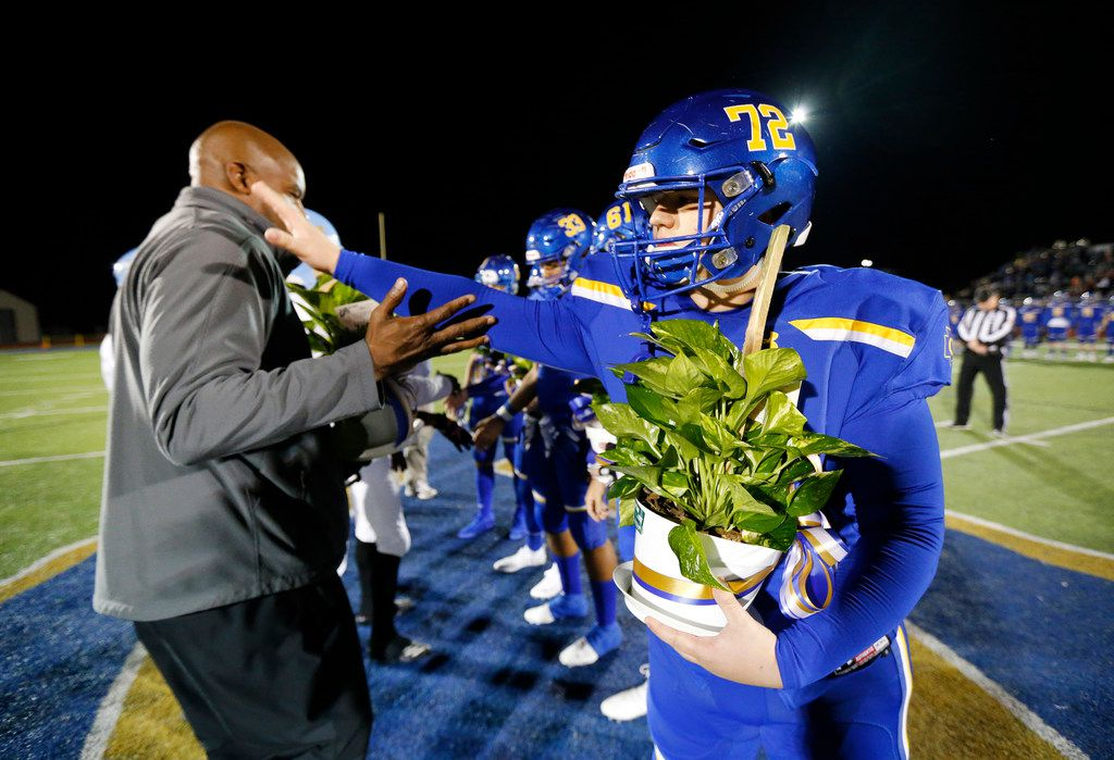 Community High football captain Eli Hartley (right) thanks Dallas Roosevelt head coach Aaron Wallace Sr (left) and his team for the plants given them during the coin toss at Community ISD Stadium in Nevada, Texas, Friday, November 8, 2019. Roosevelt captains gave them plants as Community was playing with heavy hearts after losing four classmates in a tragic vehicle accident earlier this week. (Tom Fox/The Dallas Morning News)