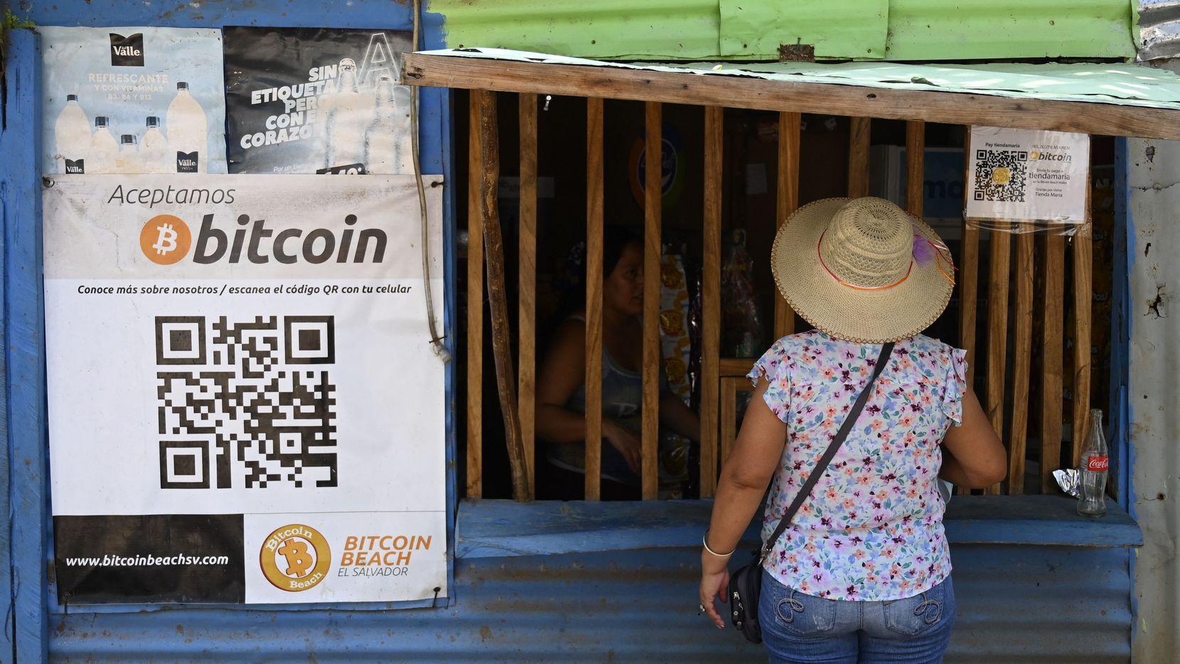 Una mujer se acerca a una tienda que acepta transacciones en Bitcoin en La Libertad, El Salvador. La criptomoneda se puede usar legalmente en ese país, pero analistas advierte de un posible impacto negativo.