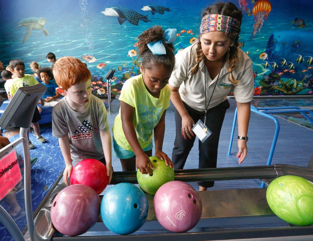 Grayson Fisher, left, and Claire Allen, center, are helped by teacher Alyssa Gomez on choosing the right ball while bowling at the Children's Learning Adventure in McKinney on June 14.. The facility has four bowling alleys.