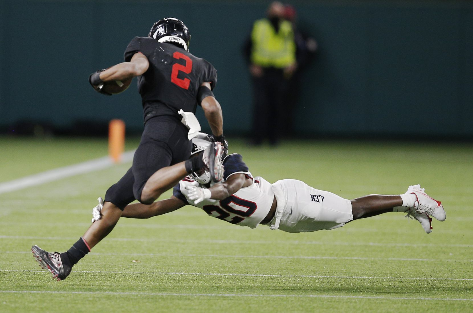 Euless Trinity junior running back Ollie Gordon (2) attempts to avoid Allen junior defensive back Sign Shuva (20) during the first half of a high school Class 6A Division I Region I semifinal football game at Globe Life Park in Arlington, Saturday, December 26, 2020. (Brandon Wade/Special Contributor)