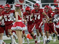 Members of the Dallas Woodrow Wilson Wildcats run onto the field before the opening kickoff of their game against Dallas Bryan Adams. The two teams played their District 6-5A Division 1 football game at Forester Field in Dallas on October 14, 2021.