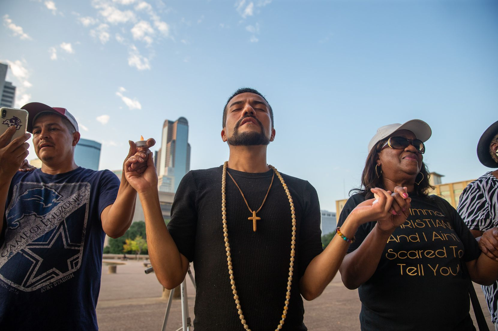 El Paso native Jaime Morales (center) sings with Abel Lopez (left) and Eva Miles (right) as they gather to honor the victims of Saturday's mass shooting in El Paso during a candlelight vigil outside Dallas City Hall in Dallas on Sunday, Aug. 4, 2019.