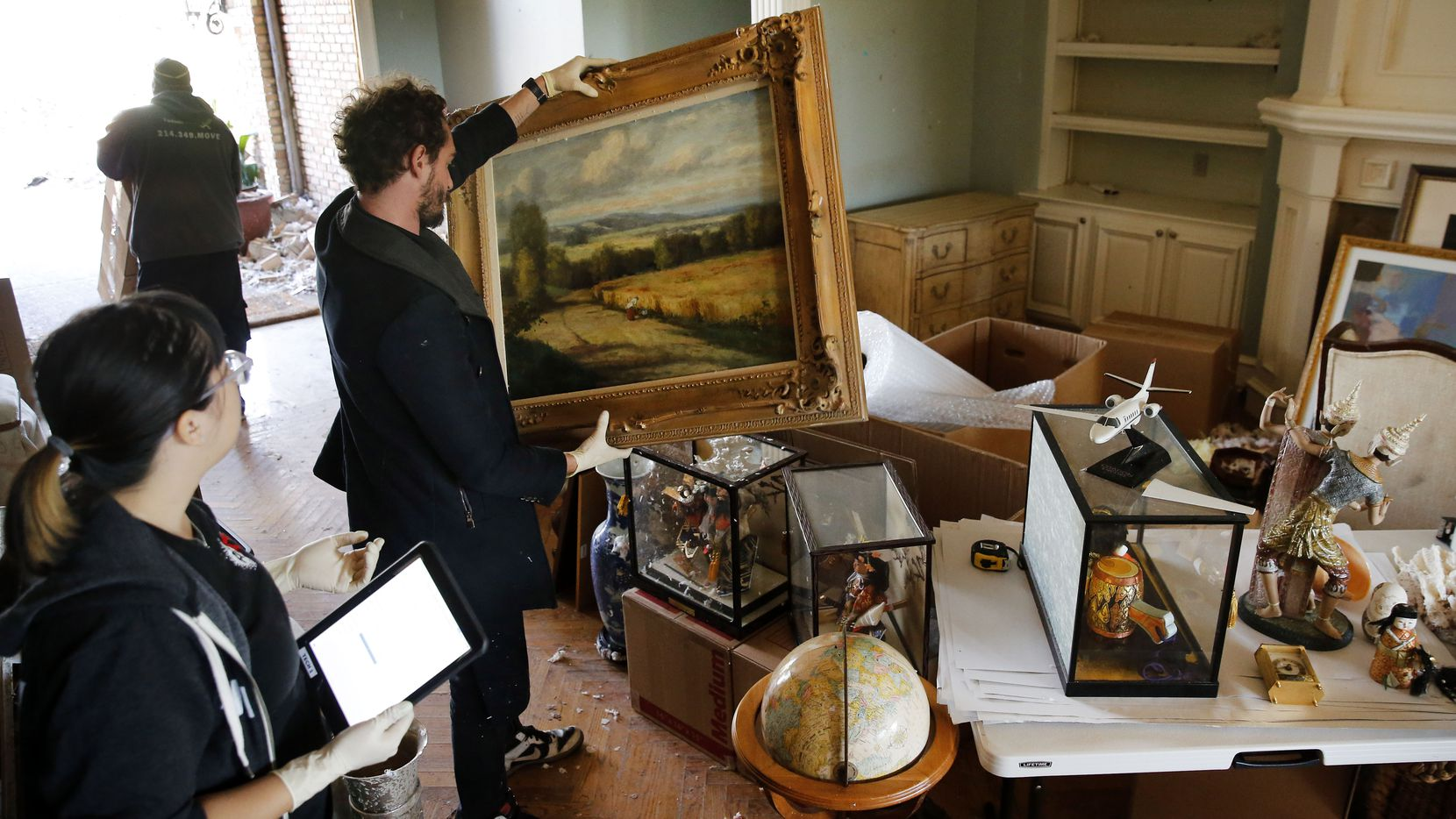 Joshua von Ammon of Art of Dallas-Fort Worth, an art recovery and restoration company, views an undamaged landscape painting in Brenda Schneider's Preston Hollow home in Dallas on Tuesday, Oct. 22, 2019.