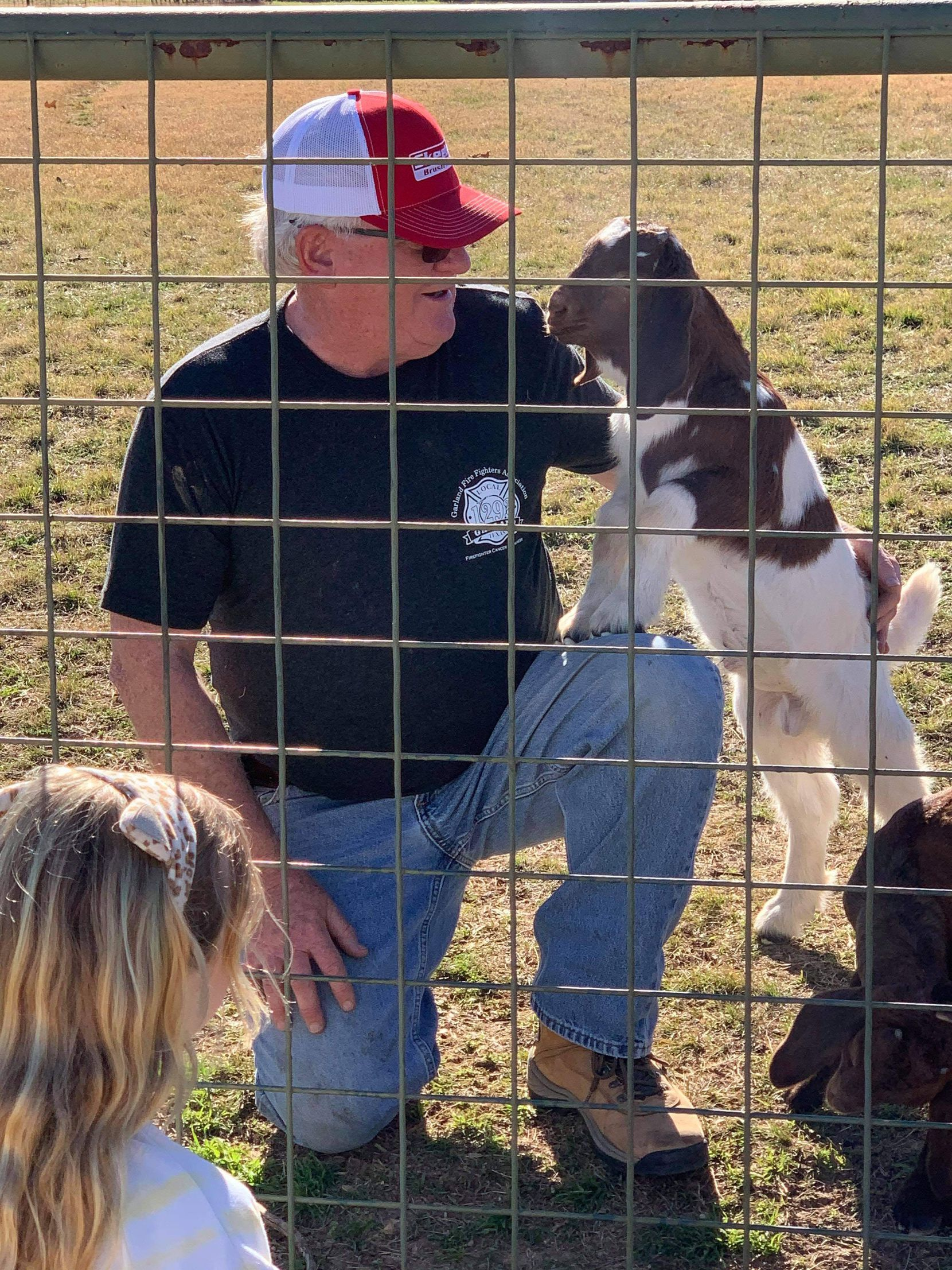 Current owner of Todd Goat Farm Mike Baker speaks with a visitor at the land's fence line.