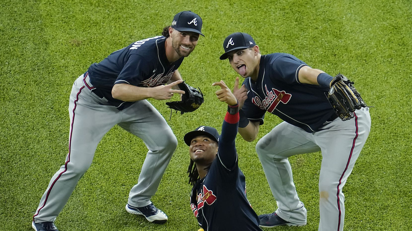 Atlanta Braves center fielder Ronald Acuna Jr. (center) pretends to take a selfie with right fielder Charlie Culberson (left) and left fielder Austin Riley (right) as the celebrate the final out of a 5-1 victory over the Los Angeles Dodgers in Game 1 of a National League Championship Series at Globe Life Field on Monday, Oct. 12, 2020.