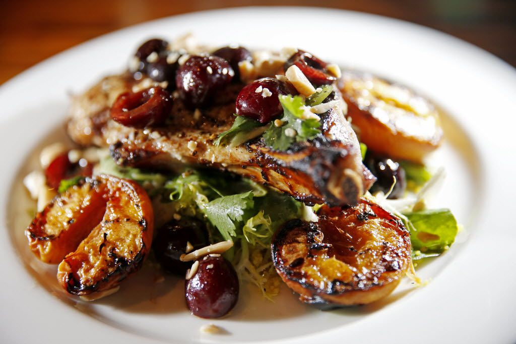 A grilled Berkshire pork chop with couscous, roasted stone fruit, watercress, cherry salsa and Marcona almonds, served last summer at Lark on the Park. (Jae S. Lee/The Dallas Morning News)