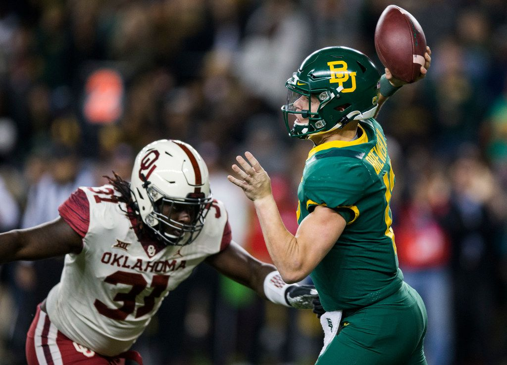 Baylor Bears quarterback Charlie Brewer (12) is threatened by Oklahoma Sooners defensive tackle Jalen Redmond (31) during the first quarter of an NCAA football game between Baylor University and Oklahoma University on Saturday, November 16, 2019 at McLane Stadium in Waco, Texas. (Ashley Landis/The Dallas Morning News)