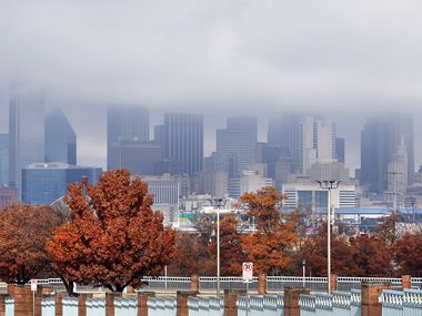 Remnants of morning rain clouds recede over bright red maples around Yvonne A. Ewell Townview Center and the Dallas skyline as a cold front pushes through North Texas on Friday, Dec. 11, 2020,