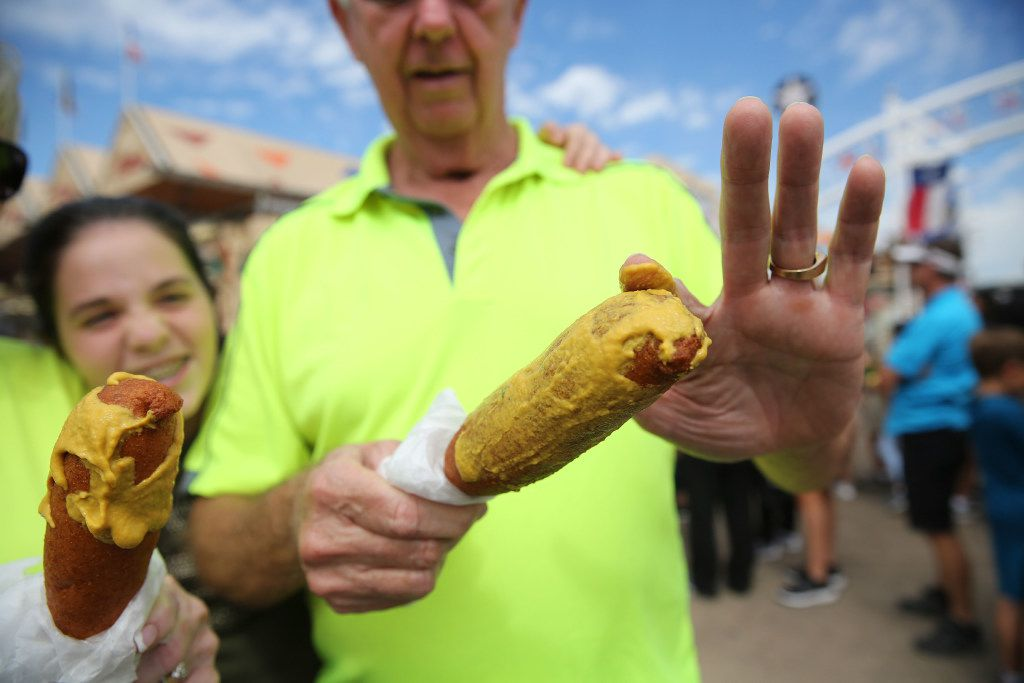 Bud Ainsworth smears mustard onto his Fletcher's corny dog at the State Fair of Texas at Fair Park in Dallas on Monday, Oct. 10, 2016. (Rose Baca/The Dallas Morning News)