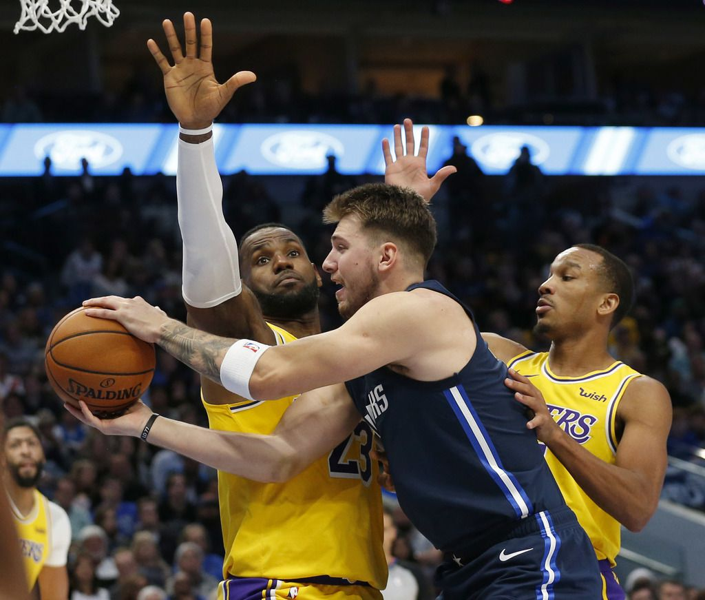 FILE - Mavericks guard Luka Doncic (77) looks to pass as he's defended by Lakers forward LeBron James (23) and guard Avery Bradley (11) during the second quarter of play at American Airlines Center in Dallas on Friday, Nov. 1, 2019.