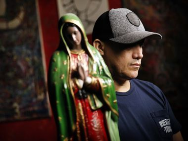 Juan, an undocumented worker, husband and father of four, is pictured with a statue of the Virgin of Guadalupe at a restaurant and bar in Dallas. He said the Virgin is his favorite santos to pray to. During the coronavirus pandemic he is only working roughly half of his full-time hours as a cook and chef. But unlike other employees with legal status in the U.S., he can't apply for unemployment benefits.