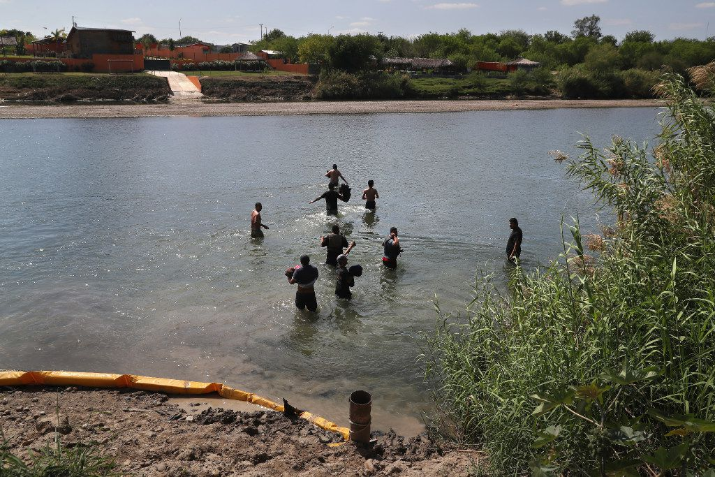 Unauthorized immigrants wade across the Rio Grande at the U.S.-Mexico border on March 14 in Roma, Texas. U.S. Border Patrol agents had intercepted them on the Texas side of the river and pushed them back into Mexico.  (Photo by John Moore/Getty Images)