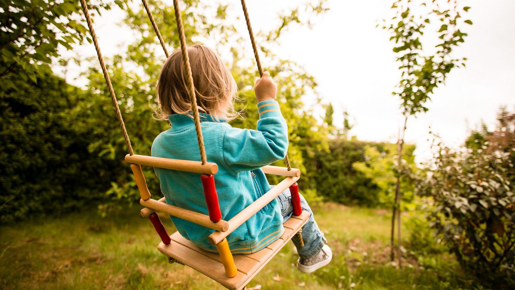 Child swinging on seesaw in backyard