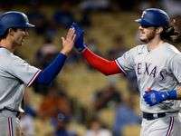 Texas Rangers' Jonah Heim, right, gets congratulations from Eli White after hitting a two-run home run against the Los Angeles Dodgers during the fourth inning of a baseball game in Los Angeles, Saturday, June 12, 2021.