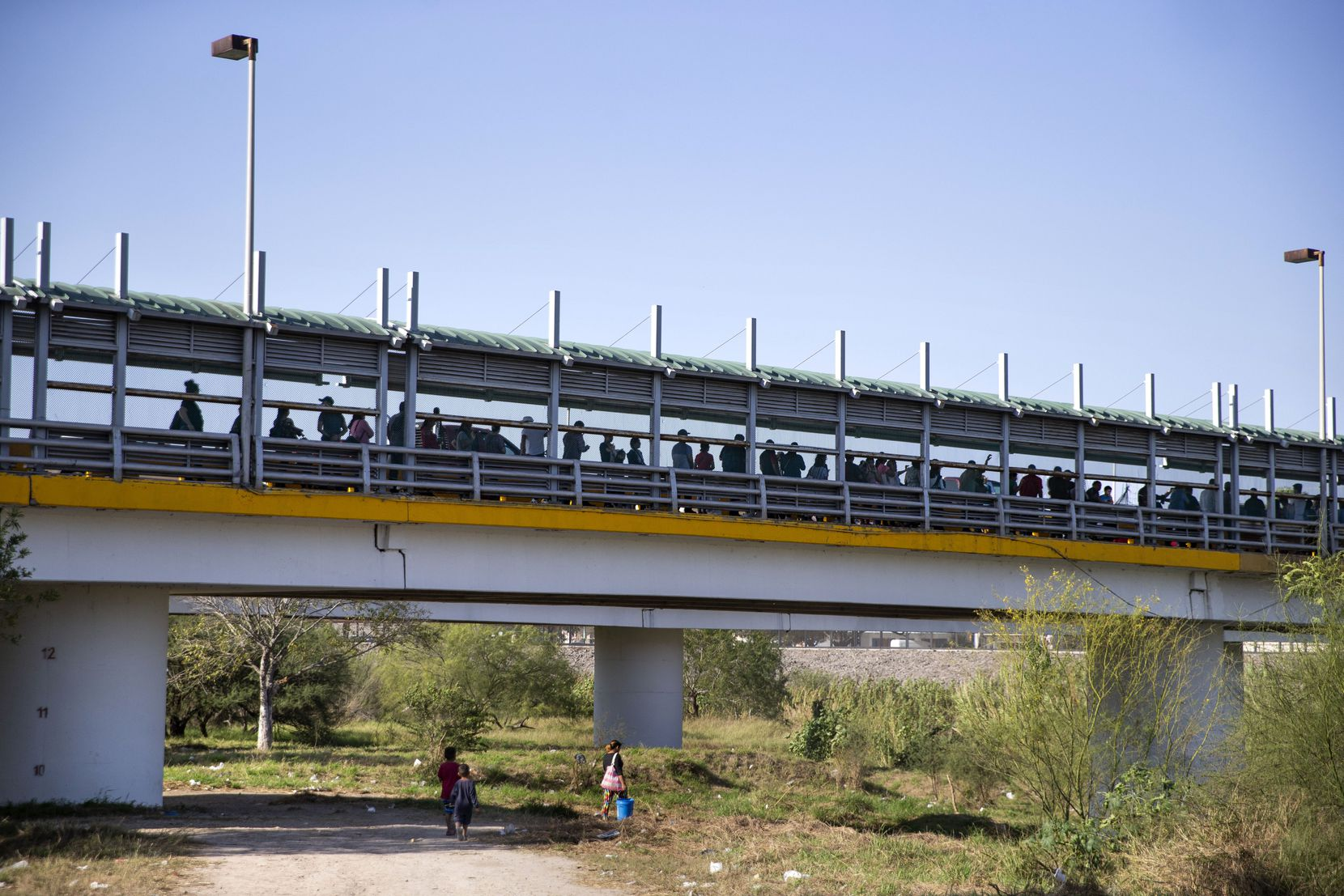The line for pedestrians to enter the U.S. at the Gateway International Bridge hovers above the river bank access trail used by asylum-seekers living at the temporary tent camps in Matamoros, Mexico, on Dec. 15, 2019.