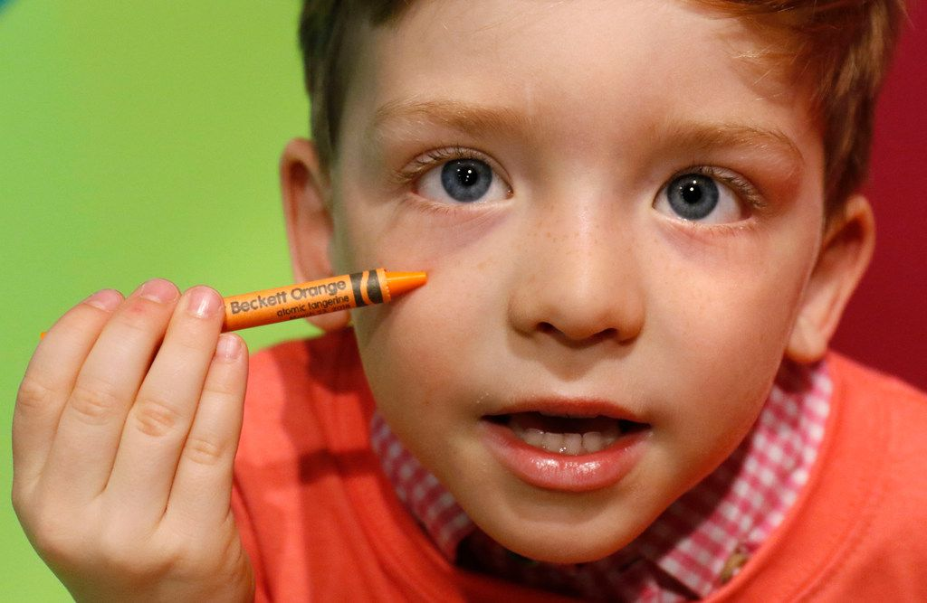 Beckett Pearson, 4, displays an orange crayon with his name printed on it at the Wrap It Up station. Personalized crayons cost one token (50 cents).