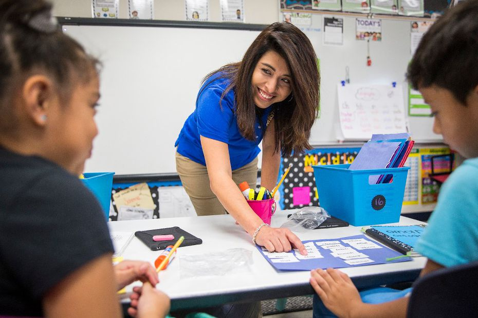 Bilingual teacher Olivia Mendez works with students in her second-grade class at Shands Elementary School in Mesquite.