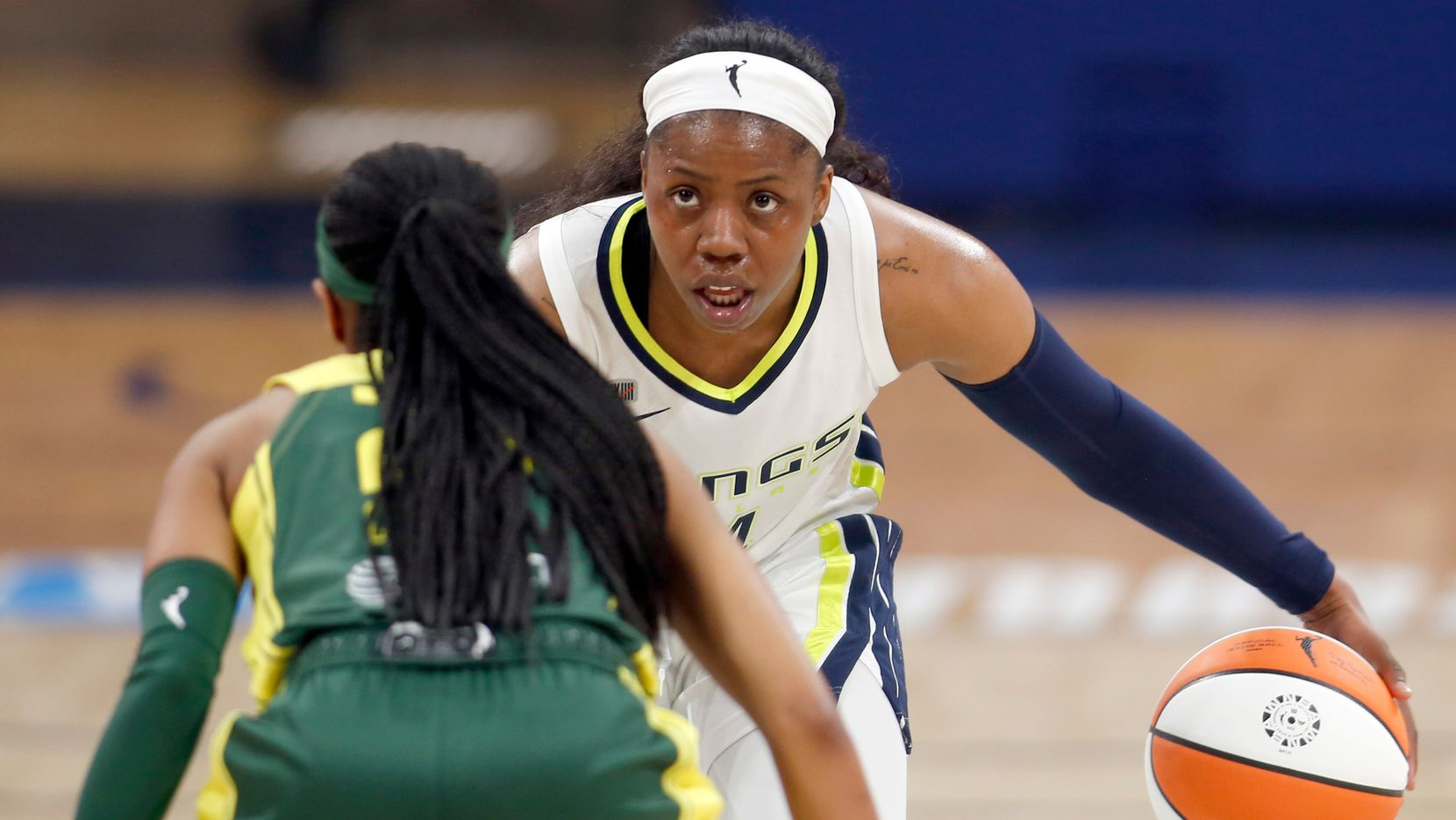 Dallas Wings guard Arike Ogunbowale (24) brings the ball to mid-court as she is defended by Seattle guard Jordin Canada (21) during first half action. The Wings hosted the Storm for their WNBA 2021season home opener at UTA's College Park Center in Arlington on May 22, 2021. (Steve Hamm/ Special Contributor)