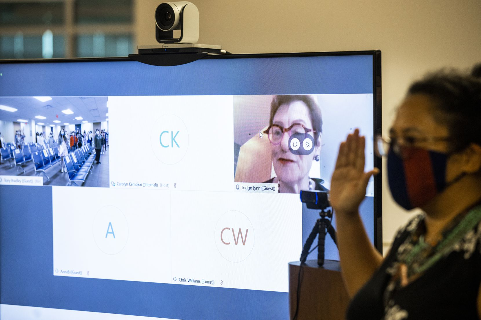 Lynn (center, on screen) virtually administers the oath of citizenship.