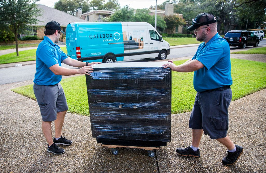 Callbox employees Jacob Huttash (left) and Ryan Seaman transport a dresser to a moving van at a client's home in Dallas. (Ashley Landis/The Dallas Morning News)