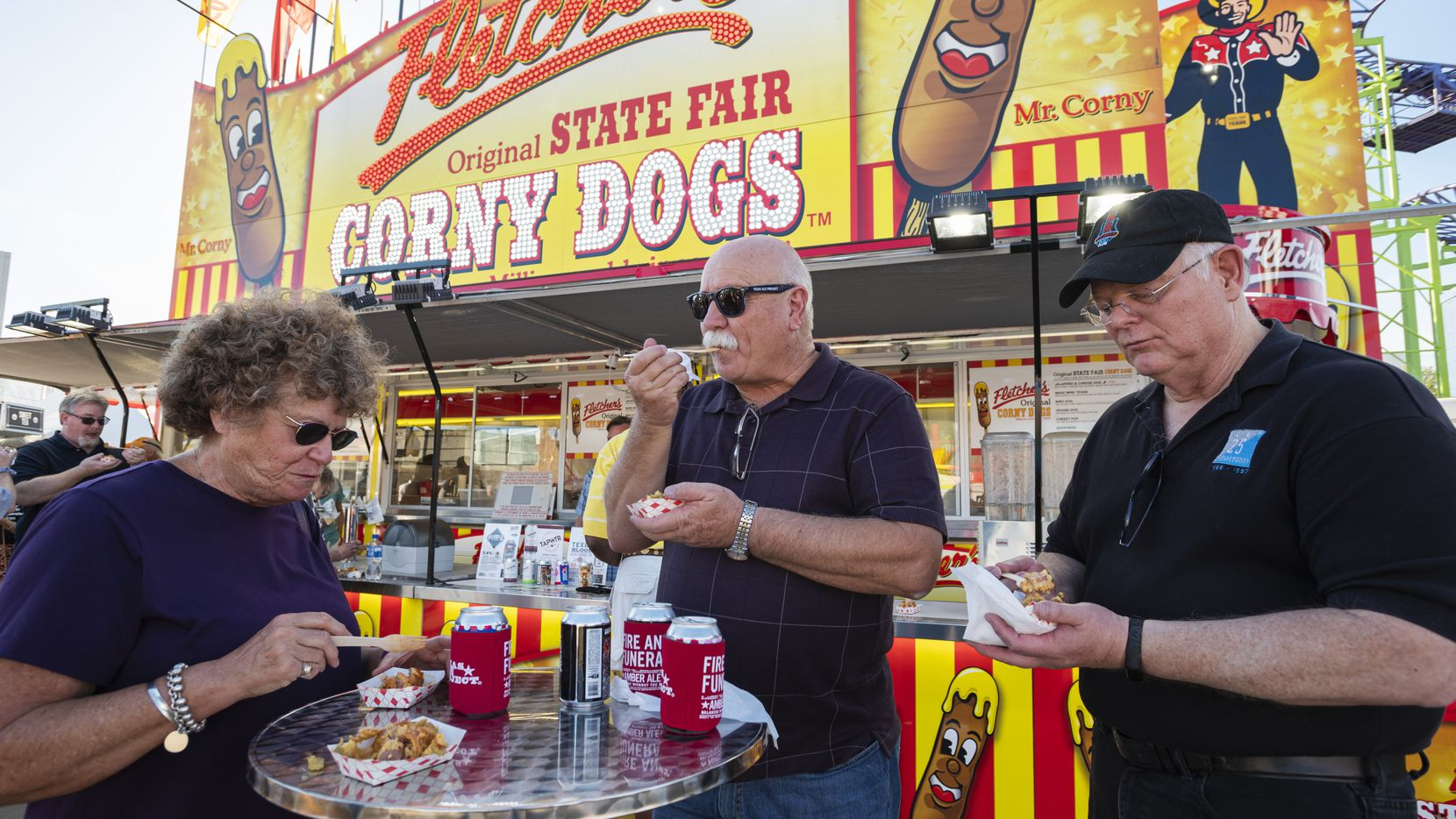 """Perri Brackett, of Lewisville, left, Rick Murray, of Alvarado, and David McKenzie of Dallas, taste test the new Fletcher's """"Dallas Hot Bird Dog"""" in front of the Fletcher's Corny Dog stand at the State Fair of Texas during a Dallas Morning News food event for DMN subscribers, on Sept. 23, 2021 in Dallas."""