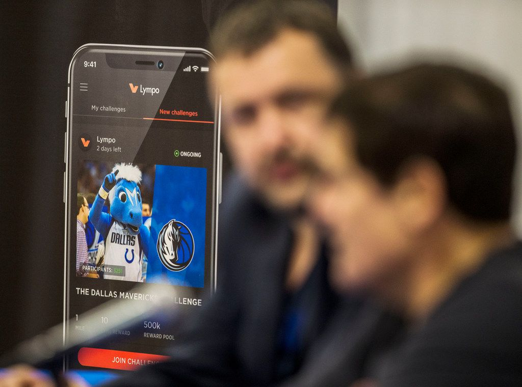 Antanas Guoga, co-founder of Lympo, left, listens to Mark Cuban, owner of the Dallas Mavericks, during a media conference at the Mavericks Training Center in Dallas on Nov. 16, 2018. The Mavericks partnered with Lympo, a fitness application that rewards its users for living a healthy lifestyle. (Carly Geraci/The Dallas Morning News)
