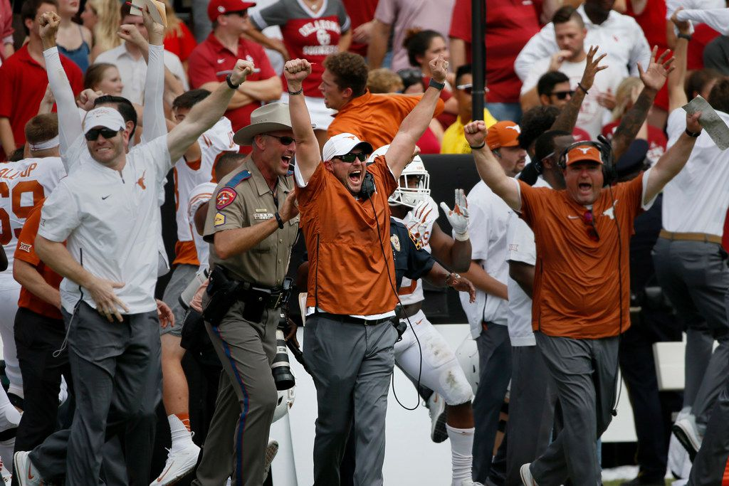 Texas Longhorns Head Coach Tom Herman (center) celebrates with other staff members after the final play of an NCAA college football game against the Oklahoma Sooners, Saturday, Oct. 6, 2018, in Dallas, Texas. The Longhorns defeated the Sooners 48-45. (AP Photo/Roger Steinman)