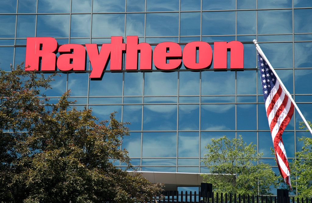 And American flag flies in front of the facade of Raytheon's Integrated Defense Systems facility, Monday, June 10, 2019, in Woburn, Mass. Raytheon Co. and United Technologies Corp. are merging in a deal that creates one of the world's largest defense companies. (AP Photo/Elise Amendola)