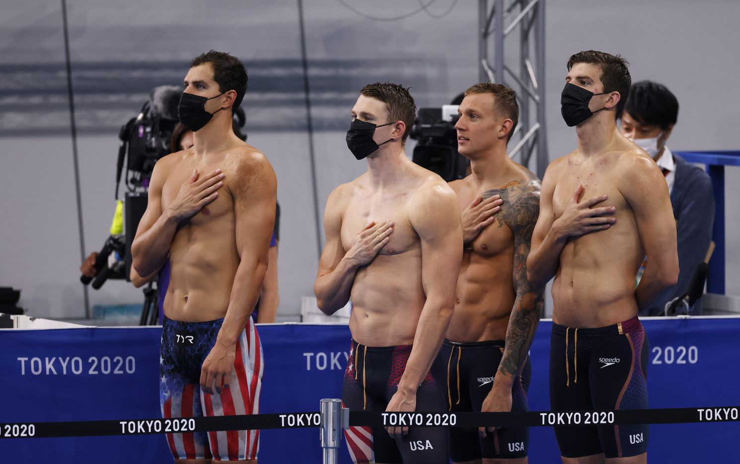 USA's Michael Andrew,  Ryan Murphy, Caeleb Dressel, and Zach Apple of the men's 4x100 meter medley relay team during the playing of the national anthem for gold medal winner Robert Finke during the men's 1500 meter freestyle medal ceremony at the postponed 2020 Tokyo Olympics at Tokyo Aquatics Centre, on Sunday, August 1, 2021, in Tokyo, Japan. (Vernon Bryant/The Dallas Morning News)