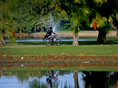A man rides a bicycle at Towne Lake Recreation Area in McKinney on July 17, 2019.