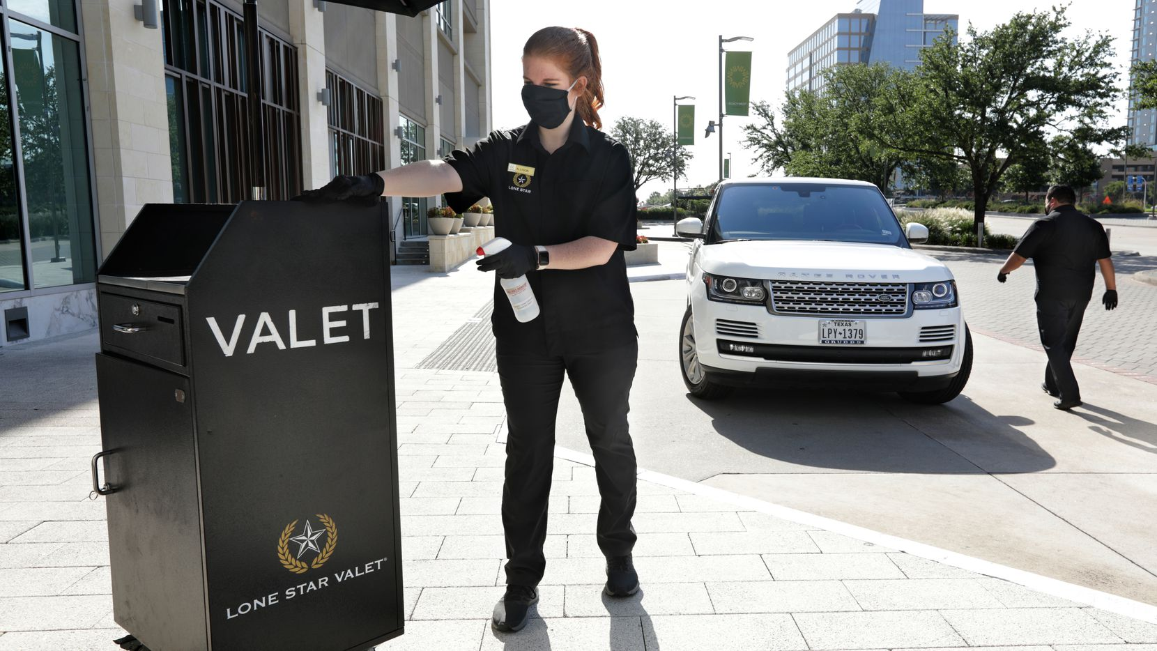 Allison Cole, left, cleans the valet booth while Gabe Munoz walks to a car at Legacy West in Plano. (Jason Janik/Special Contributor)