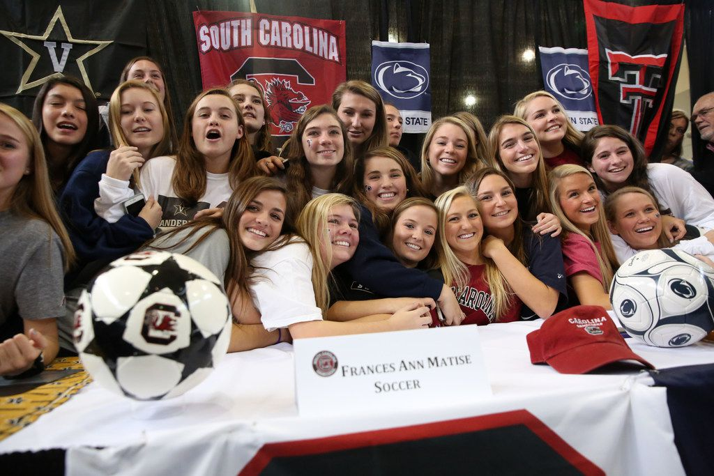 The Highland Park girls soccer team poses for a photograph with the four signees during Highland Park High School's National Signing Day ceremony at the school in Dallas on Wednesday, Feb. 7, 2018. (Rose Baca/The Dallas Morning News)
