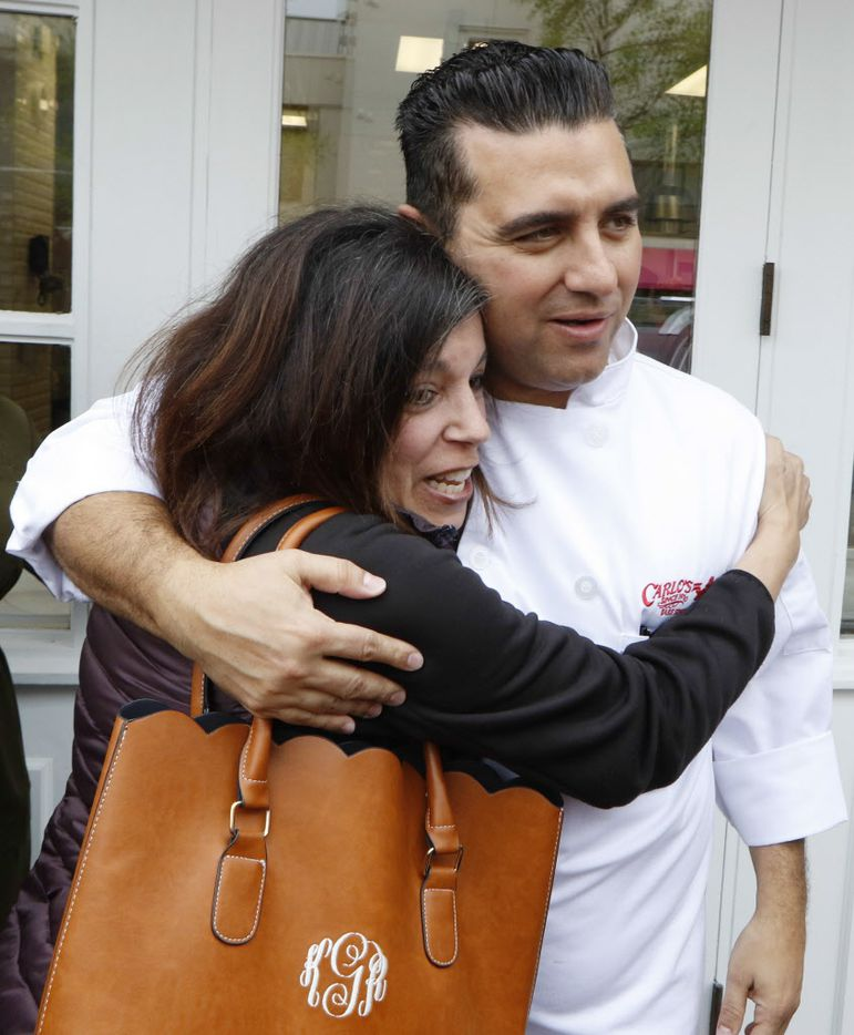Karen Gullatt, left, hugs Buddy Valastro at Carlo's Bakery on Friday.