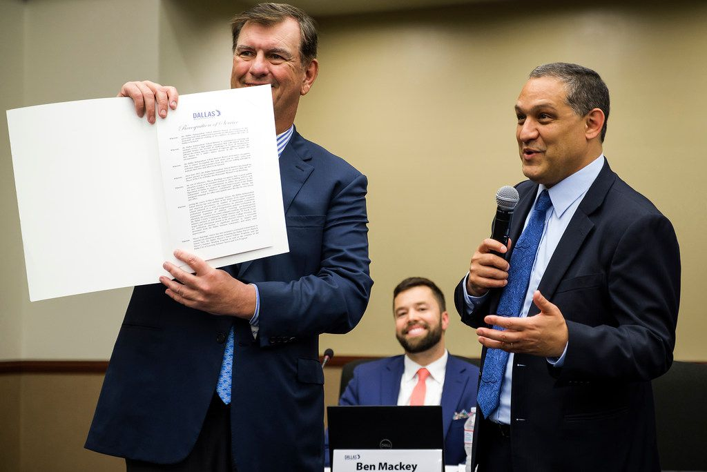 Dallas Mayor Mike Rawlings displays his Recognition of Service proclamation presented to him by DISD Board President Edwin Flores during a DISD board meeting as trustee Ben Mackey looks on Thursday.