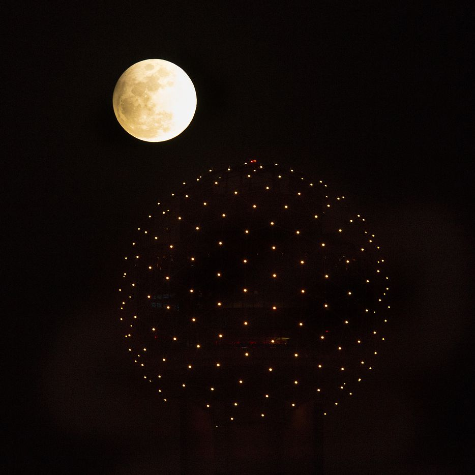 A penumbral eclipse (partial lunar eclipse) is seen as the full moon rises over the lights of the ball on top of Reunion Tower in downtown Dallas on, Feb. 10, 2017.