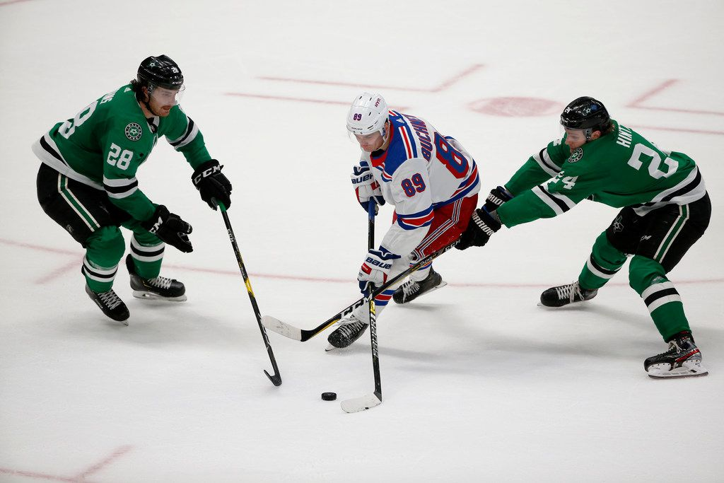 New York Rangers right wing Pavel Buchnevich (89) tries to get the puck past Dallas Stars defenseman Stephen Johns (28) and left wing Roope Hintz (24) during the second period of an NHL hockey game in Dallas, Tuesday, March 10, 2020. (AP Photo/Michael Ainsworth)