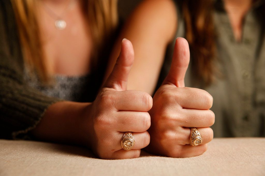 """Texas A&M University alumnae Meghan Romere (left) and Abbie Hillis wear their class rings while showing the school's """"gig 'em"""" sign. They are fighting for change in the university's handling of sexual assaults."""