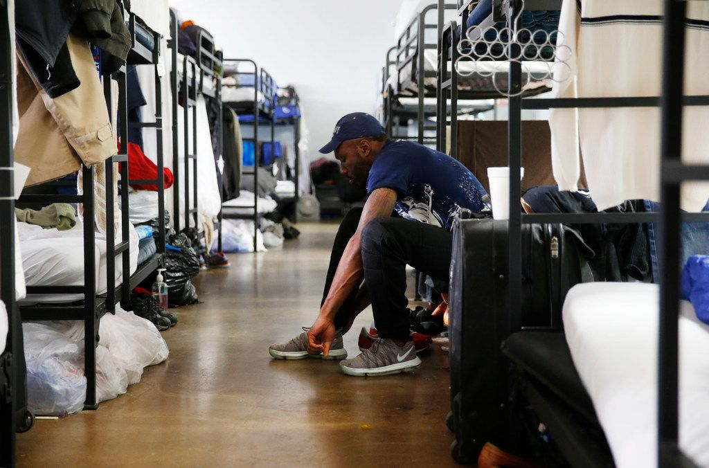 Isaac Amos prepares for work by putting his shoes on in the emergency shelter room of the Carr P. Collins Social Service Center operated by the Salvation Army in Dallas. This section of the building can sleep up to 60 people.