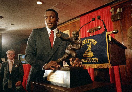 ORG XMIT: *S0426449919* FILE - In this Dec. 5, 1987 file photo, Notre Dame's wide receiver and kick return specialist Tim Brown poses with the Heisman Trophy after being named 1987's best college football player at New York's Downtown Athletic Club.  Brown is among 16 players to be elected to the College Football Hall of Fame, it was announced Thursday, APril 30, 2009. (AP Photo/Ron Frehm, File) NY151 12052012xSPORTS 08232015xPUB