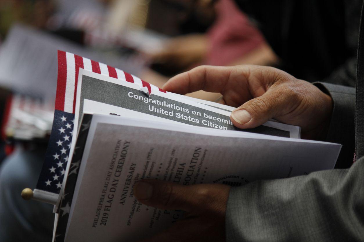 Una persona con documentos en una ceremonia de naturalización.