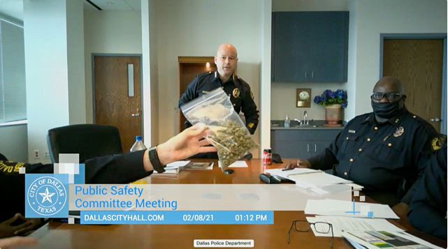 A bag of marijuana is held up during Dallas Police Chief Eddie Garcia's first public safety committee meeting as chief, which was held virtually, in Dallas on Feb. 8, 2021.