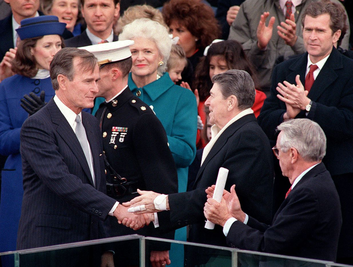 Outgoing President Ronald Reagan greets newly inaugurated President George H.W. Bush as first lady Barbara Bush (center), Marilyn Quayle (far left), and son George W. Bush (top right) applaud during Bush's swearing-in ceremony, Jan. 20, 1989, in Washington, D.C.