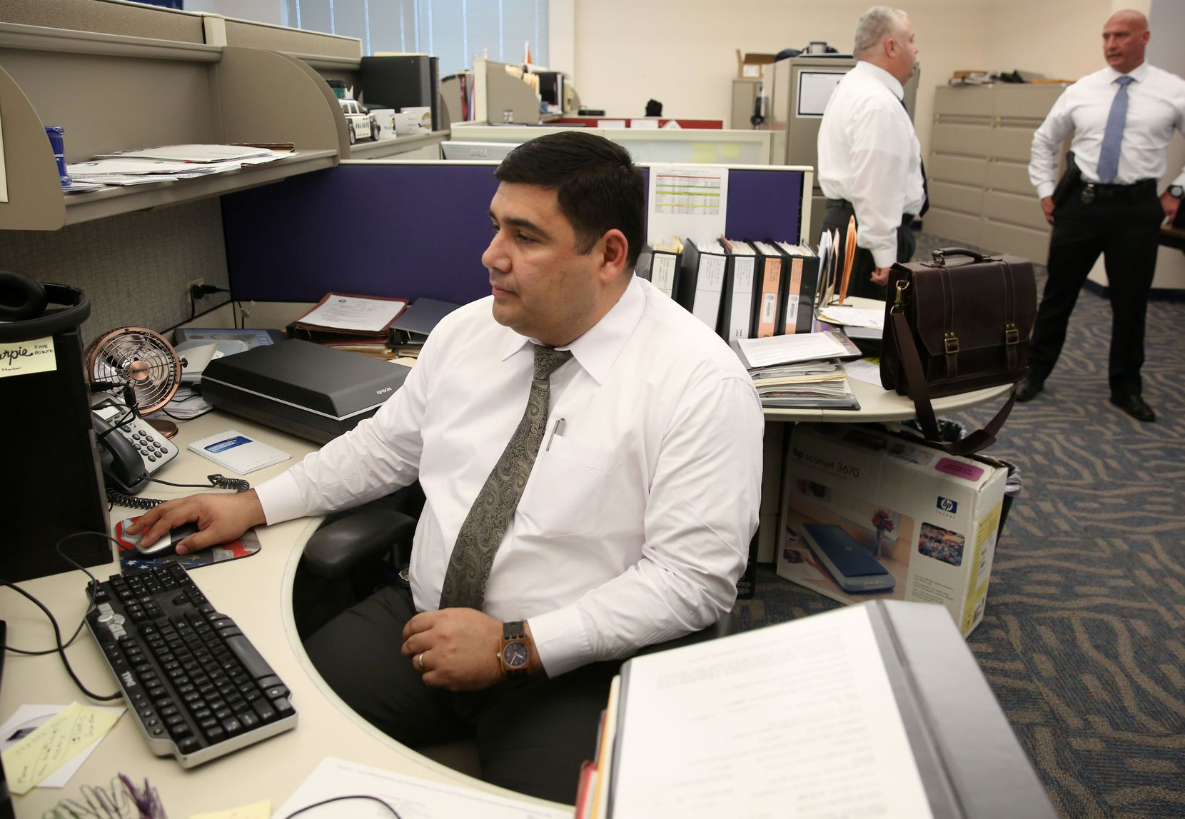 Detective Noe Camacho, a member of the cold case unit, works at his desk at Dallas Police Department headquarters.
