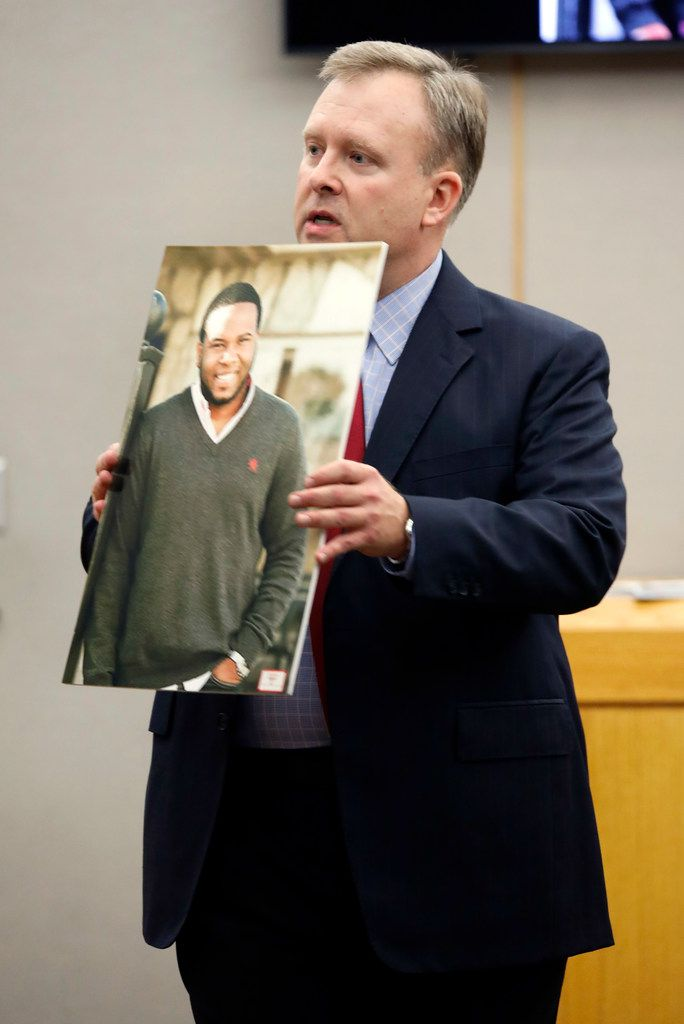 Assistant District Attorney Jason Hermus shows a photo of Botham Jean to the jury during his opening statement Monday.