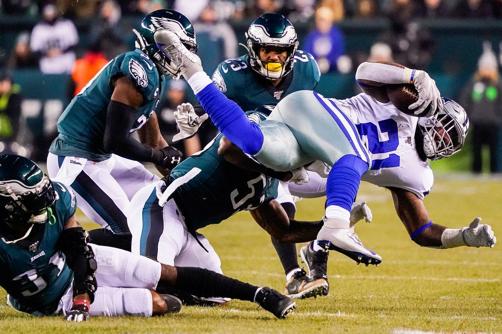 Dallas Cowboys running back Ezekiel Elliott (21) is upended by Philadelphia Eagles cornerback Jalen Mills (31) during the first half of an NFL football game at Lincoln Financial Field on Sunday, Dec. 22, 2019, in Philadelphia. (Smiley N. Pool/The Dallas Morning News)