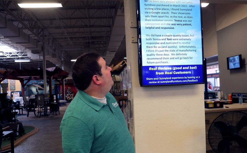 In this Tuesday, Dec. 11, 2018, photo Brad Schweig, co-owner of Sunnyland Furniture, looks at a video screen displaying a review of his business in Dallas.